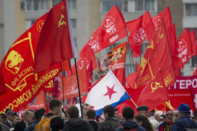 <p>People march with a former Soviet navy and red flags during a Communist rally to mark May Day in Moscow, Russia, May 1, 2018. More than 100,000 people came out on the streets on Moscow to march in the traditional May Day parade. (Photo: Alexander Zemlianichenko/AP) </p>