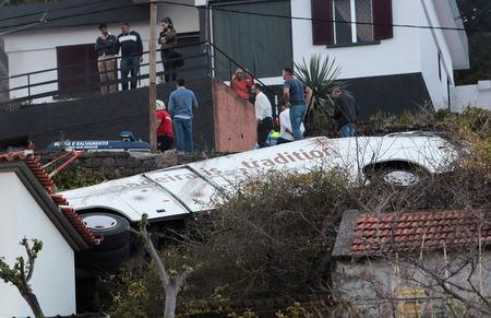People stand next to the wreckage of a bus after an accident in Canico, in the Portuguese Island of Madeira, April 17, 2019. REUTERS/Duarte Sa