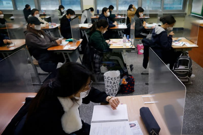 A student checks the time as the others wait for the start of the annual college entrance examinations amid the coronavirus disease (COVID-19) pandemic at an exam hall in Seoul