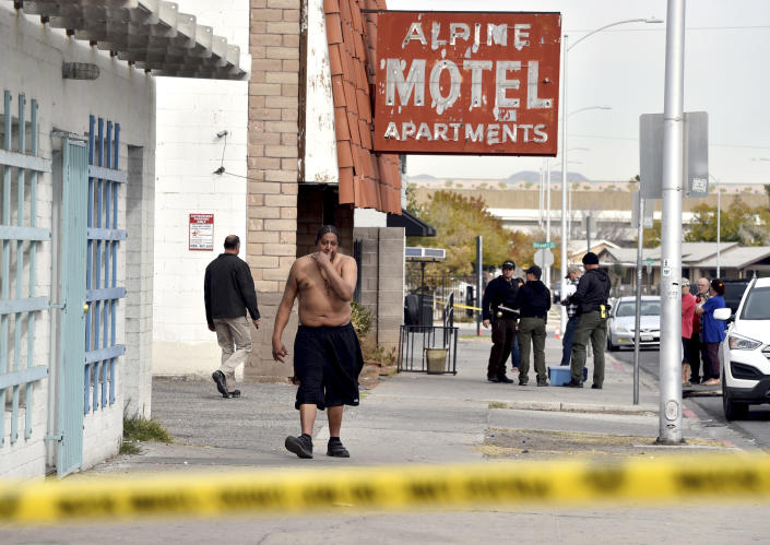 Anthony Todd Meadows, second left, walks from his residence after a fire displaced him from a three-story apartment building early Saturday, Dec. 21, 2019 in Las Vegas. The fire was in first-floor unit of the Alpine Motel Apartments and its cause was under investigation, the department said. Authorities say multiple fatalities were reported and many more were injured. (AP Photo/David Becker)