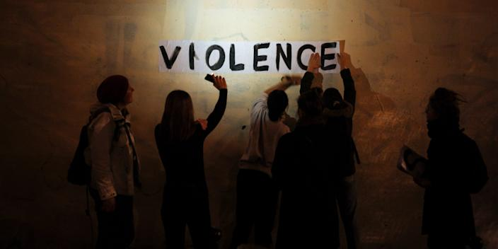 """In this Oct. 31, 2019 photo, the word """"violence"""" is pasted onto a wall by a group of women in a dark street in Paris. In Paris and cities across France, the signs are everywhere."""