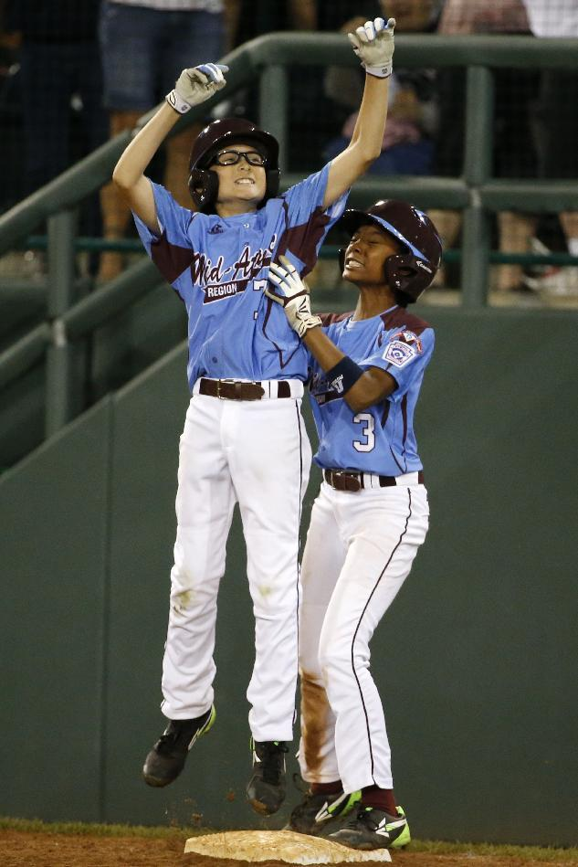 Philadelphia's Tai Shanahan (7) celebrates his walk-off single with teammate Mo'ne Davis (3) during the sixth inning of a baseball game against Pearland in United States pool play at the Little League World Series tournament in South Williamsport, Pa., Sunday, Aug. 17, 2014. Philadelphia won 7-6. (AP Photo/Gene J. Puskar