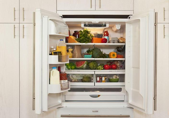 """<p>To <a href=""""https://www.bhg.com/homekeeping/house-cleaning/tips/how-to-clean-a-refrigerator/"""" rel=""""nofollow noopener"""" target=""""_blank"""" data-ylk=""""slk:properly clean your refrigerator"""" class=""""link rapid-noclick-resp"""">properly clean your refrigerator</a>, <em>Better Homes & Gardens</em> suggests that you first remove and hand-wash removable refrigerator shelves, wire racks, and drawers in hot water and mild dish soap. Cover stubborn food spills with a warm, wet cloth for a few minutes to soften the spills before tackling with a non-abrasive scrubber.</p><p>For drawers and shelves you can't remove, get them clean using a mixture of one part baking soda and seven parts water. Once you've rinsed and dried all surfaces, deodorize your refrigerator by filling an open container with dry baking soda and leaving it on the bottom shelf. </p>"""
