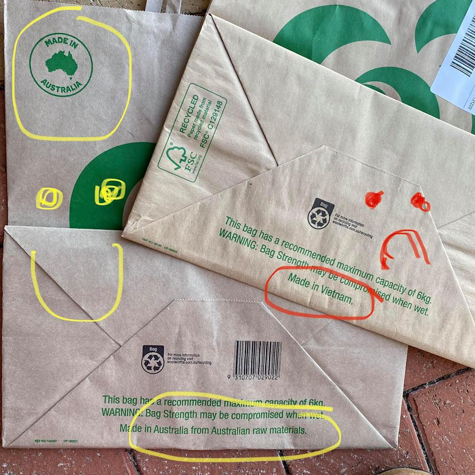 A photo taken by a Woolworths customer showing the new manufacturing country of the paper bag and an old bag that is