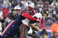Tampa Bay Buccaneers quarterback Tom Brady, right, is sacked by New England Patriots outside linebacker Matt Judon, left, during the first half of an NFL football game, Sunday, Oct. 3, 2021, in Foxborough, Mass. (AP Photo/Elise Amendola)