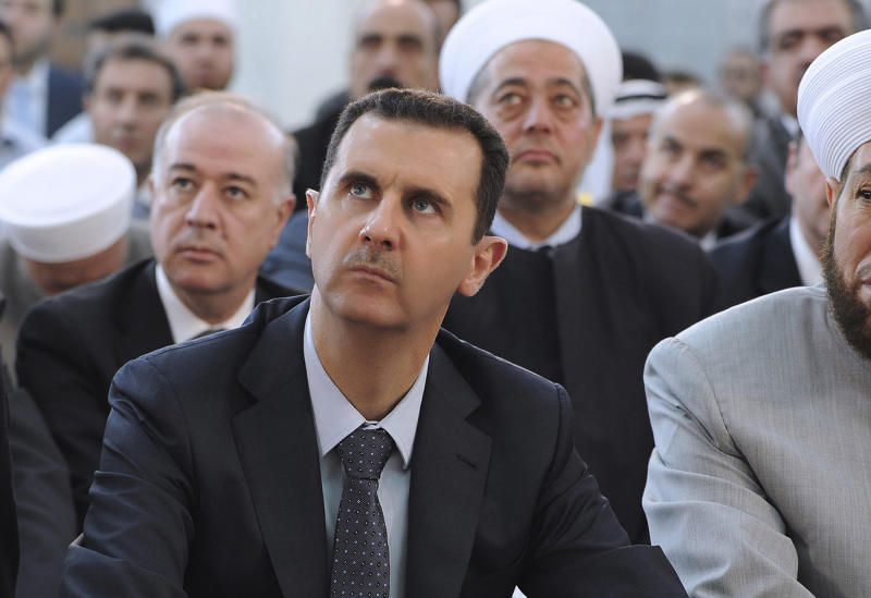 In this photo provided by the Syrian official news agency SANA, Syrian President Bashar Assad performs Eid prayers in the Hamad Mosque in Damascus, Syria, Sunday, Aug. 19, 2012. Assad prayed early on Sunday at the start of Eid al-Fitr, a three-day holiday marking the end of the holy month of Ramadan. The last time he appeared in public was on Wednesday, July 4, 2012, when he gave a speech in parliament. (AP Photo/SANA)