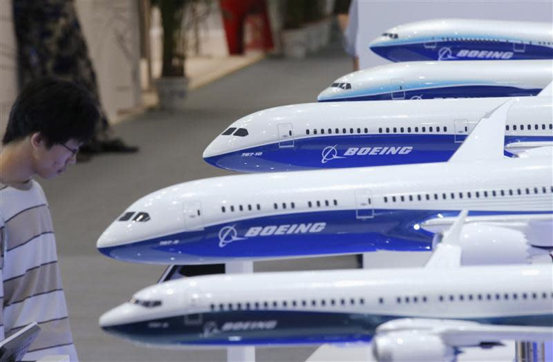 File photo of a visitor looking at a display of miniature Boeing passenger aircrafts at Aviation Expo China 2013 in Beijing