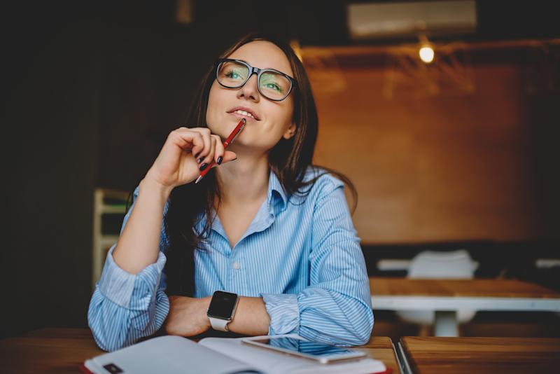 Dreamy woman podring while working on journalistic publication sitting with notebook in cafe,thoughtful female student in eyewear doing homework task solving problems and analyzing information