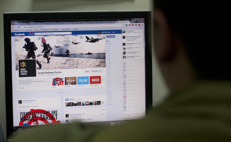 An Israeli soldier poses as he looks at the Facebook page of the IDF, at the IDF spokesperson office in Jerusalem, Thursday, Nov. 15, 2012. The hostilities between Israel and Hamas have found a new battleground in social media, as both the Israeli Defense Force and Hamas militants have exchanged fiery tweets throughout the fighting in an online war to influence public opinion. (AP Photo/Sebastian Scheiner)