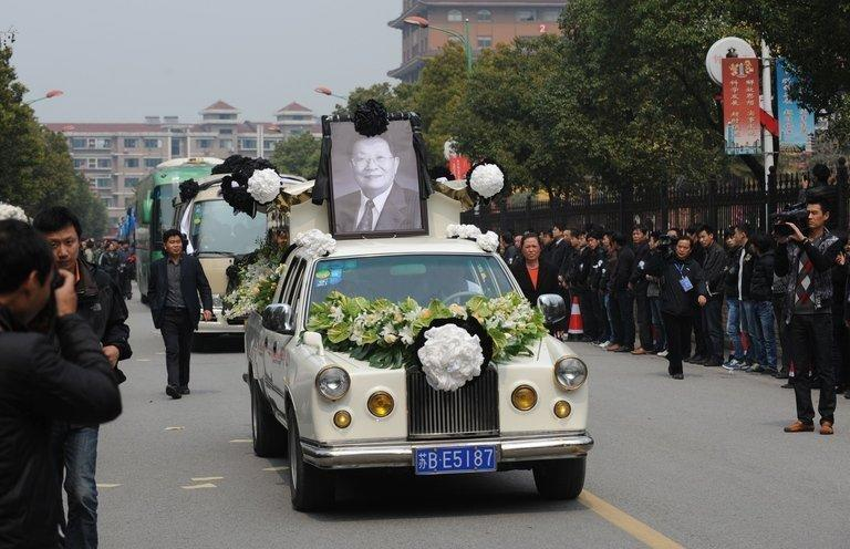 """The coffin of retired local Communist Party chief Wu Renbao is driven through the Huaxi village on March 22, 2013. Residents of China's """"richest village"""" bid farewell to the man who made Huaxi a socialist paradise, with a 20-vehicle funeral procession transporting his coffin and a helicopter flying overhead"""