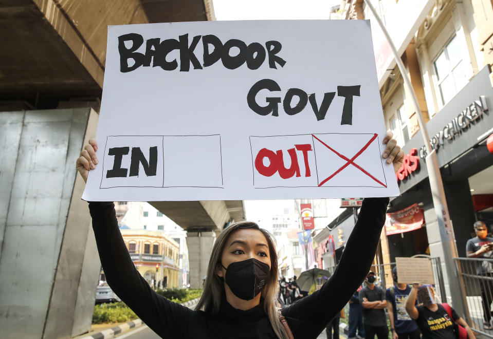 A protester holds a placard during a demonstration demanding the prime minister step down near the Independence Square in Kuala Lumpur, Saturday, July 31, 2021. Hundreds of black-clad Malaysian youths have rallied in the city center, demanding Prime Minister Muhyiddin Yassin resign for mismanaging the coronavirus pandemic that has worsened. (AP Photo/FL Wong)