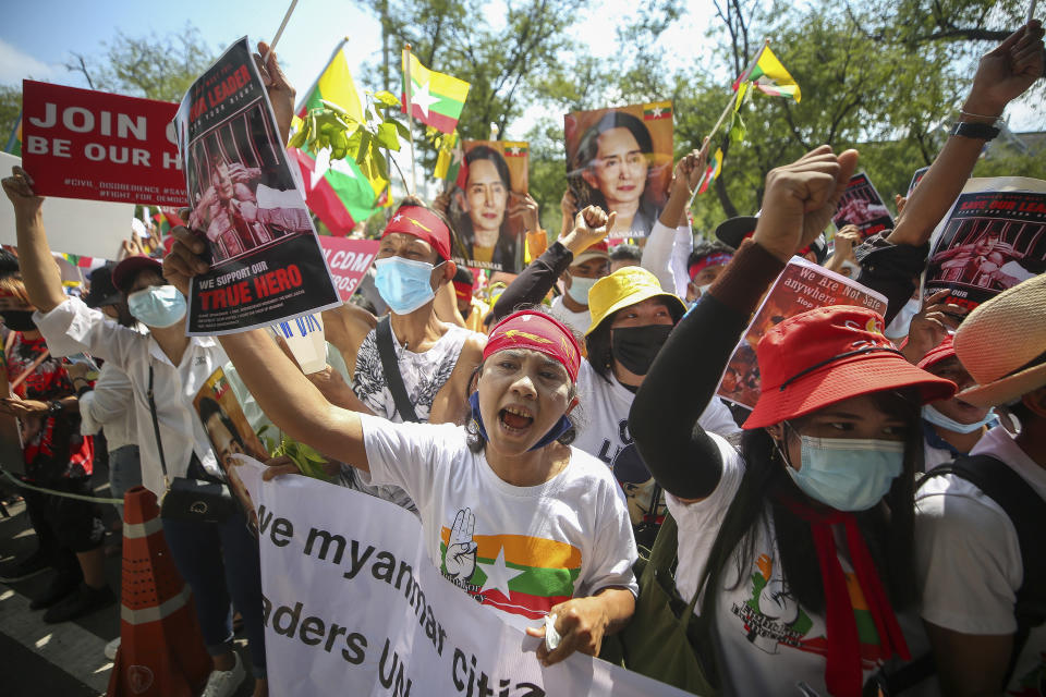 Myanmar nationals living in Thailand hold pictures of deposed Myanmar leader Aung San Suu Kyi as they protest against the military coup in front of the United Nations building i in Bangkok, Thailand, Sunday, March 7, 2021. (AP Photo/Nava Sangthong)