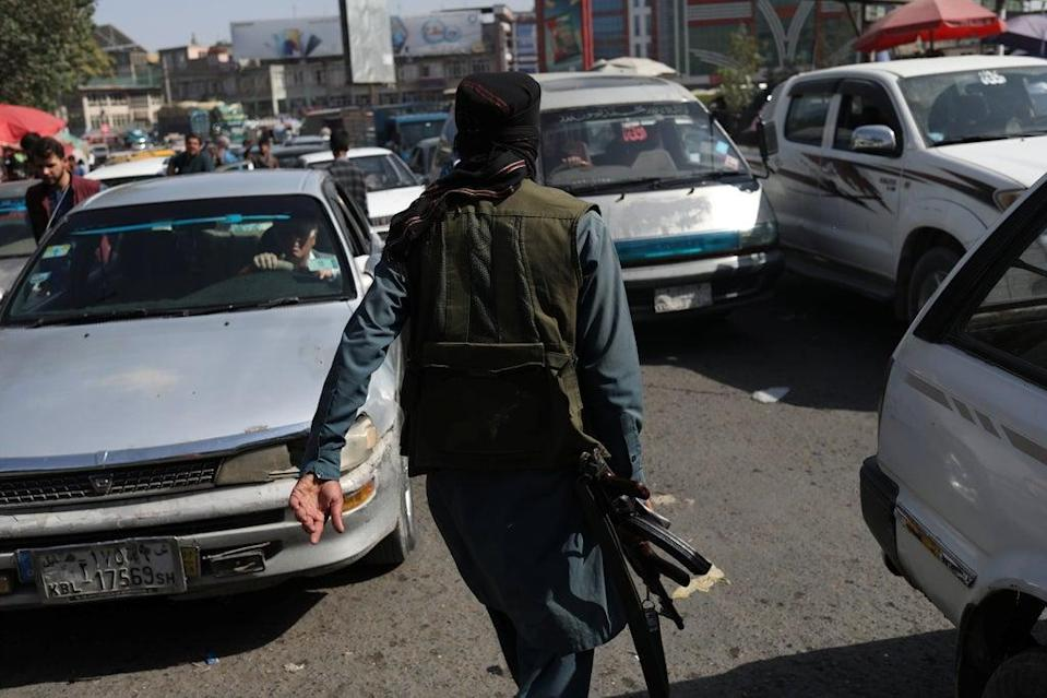 A member of the Taliban directs traffic in Kabul (via REUTERS)