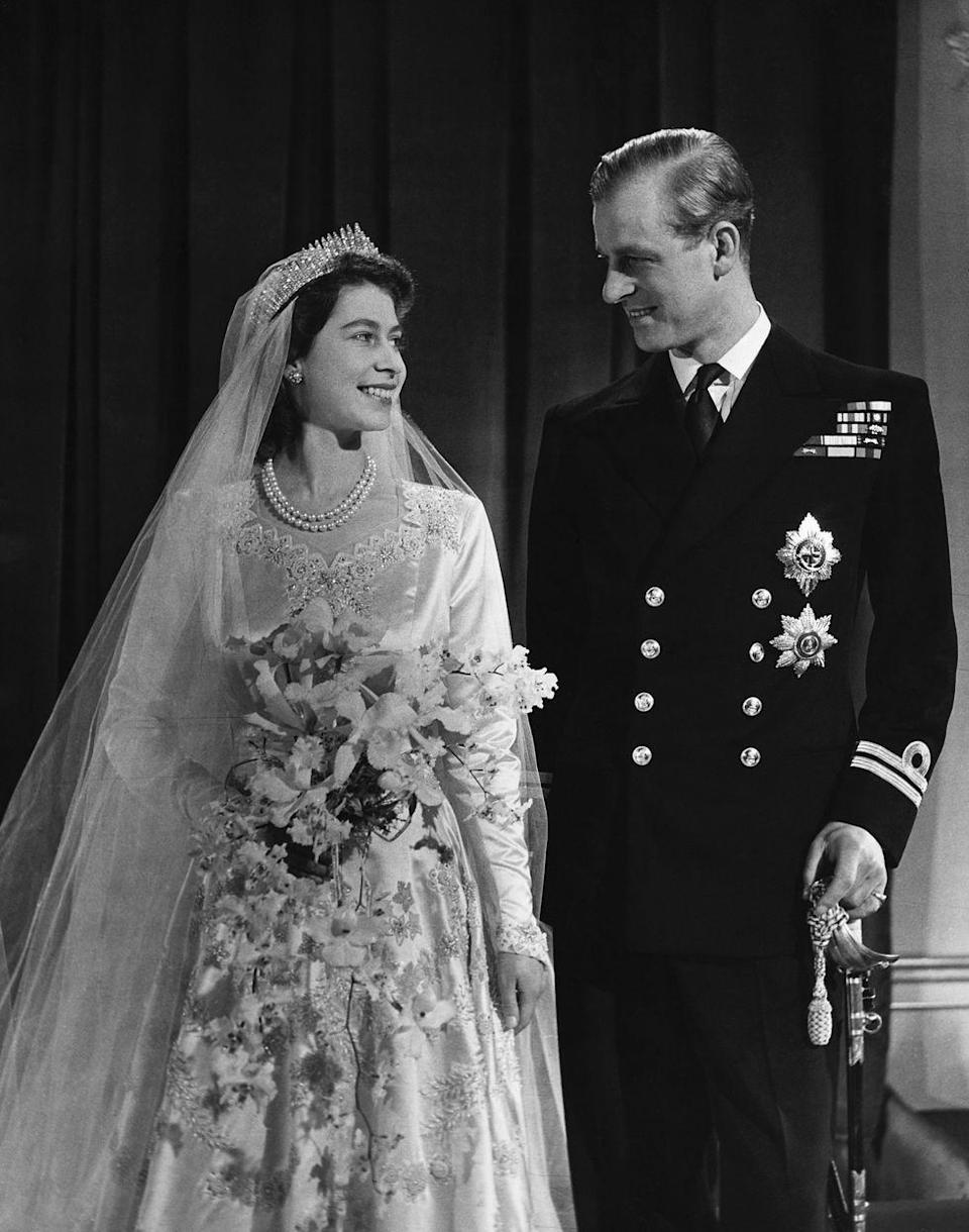 """<p>Elizabeth and Philip share a sweet moment on their wedding day. The couple tied the knot at Westminster Abbey on November 20, 1947. The future Queen's <a href=""""http://www.townandcountrymag.com/society/tradition/a13438510/queen-elizabeth-wedding-dress/"""" rel=""""nofollow noopener"""" target=""""_blank"""" data-ylk=""""slk:wedding gown"""" class=""""link rapid-noclick-resp"""">wedding gown</a> included 10,000 seed pearls and a 15-foot train. </p>"""