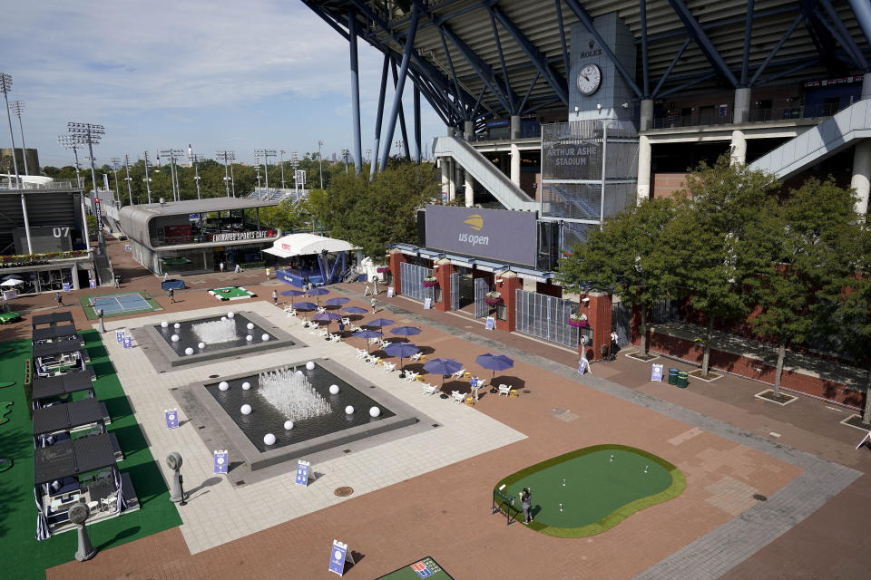 USTA event personnel walk through the main plaza outside Arthur Ashe Stadium before the second round of the US Open tennis championships, Thursday, Sept. 3, 2020, in New York. The plaza, normally bustling with tennis fans, has been converted into a lounge and playground for the players this year. (AP Photo/Seth Wenig)