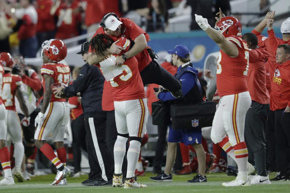 Kansas City Chiefs' Cameron Erving, gives a coach a lift on the sideline during the second half of the NFL Super Bowl 54 football game against the San Francisco 49ers Sunday, Feb. 2, 2020, in Miami Gardens, Fla. (AP Photo/John Bazemore)