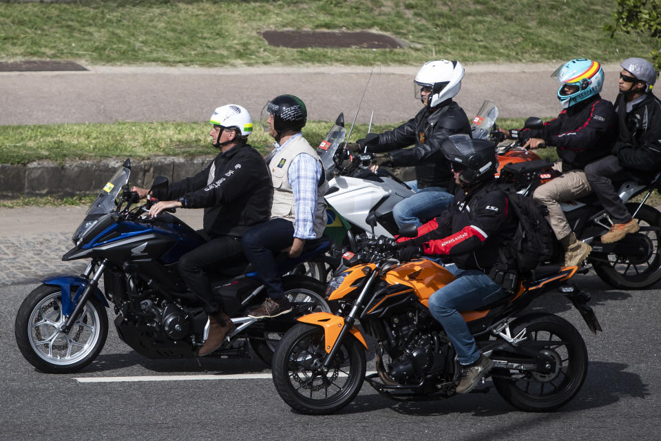 Brazil's President Jair Bolsoanro, in front, takes a motorcycle tour with supporters, in Rio de Janeiro, Brazil, Sunday, May 23, 2021. (AP Photo/Bruna Prado)