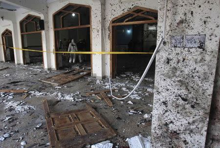 Security officials stand in cordoned areas as they look for evidence amid the damage after an explosion in a Shi'ite mosque in Peshawar