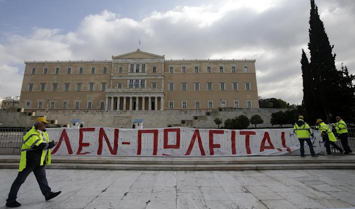 Protesters hang a banner reads ''Not for Sale'' during a rally by hundreds of striking port workers outside the Greek Parliament in Athens, on Wednesday, Feb. 26, 2014. Greek dock workers across the country walked off the job Wednesday in a 24-hour strike to protest plans to sell a stake in the Piraeus Port Authority, the country's largest port. Privatizing state-held assets is a key part of Greece's international bailout agreement. (AP Photo/Thanassis Stavrakis)