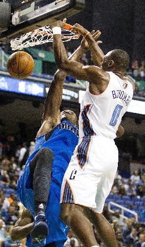 Charlotte Bobcats' Bismack Biyombo (0) dunks over Dallas Mavericks' Samuel Dalembert (1) in first half of a preseason NBA game at the Greensboro Coliseum in Greensboro, N.C., Saturday, Oct. 19, 2013. (AP Photo/Lynn Hey)