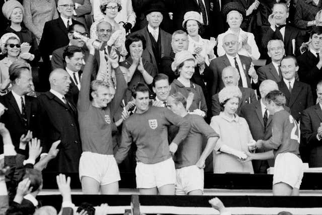 Hunt received a medal from the Queen while captain Bobby Moore celebrated after the 1966 final