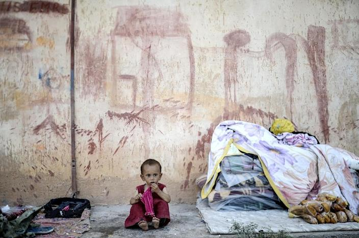 A Syrian refugee baby sits in front of a wall near the Turkish border post of Akcakale, province of Sanliurfa, on June 17, 2015 (AFP Photo/Bulent Kilic)