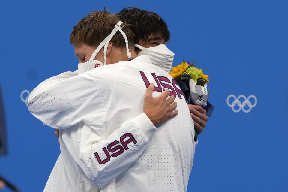 Gold medalist Chase Kalisz, left, of the United States, embraces teammate and silver medalist Jay Litherland, during the medal ceremony for the the men's 400-meter individual medley at the 2020 Summer Olympics, Sunday, July 25, 2021, in Tokyo, Japan. (AP Photo/Martin Meissner)