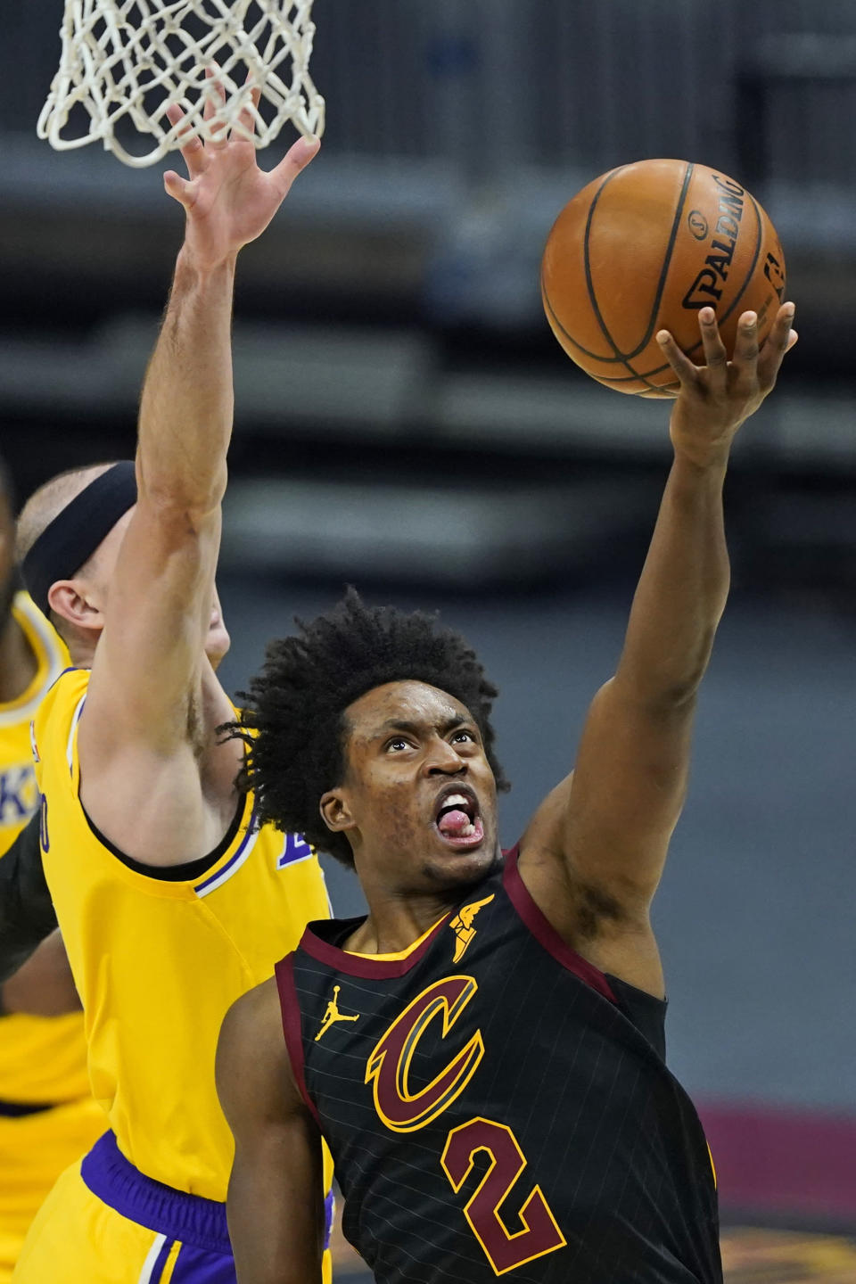 Cleveland Cavaliers' Collin Sexton, right, drives to the basket against Los Angeles Lakers' Alex Caruso in the first half of an NBA basketball game, Monday, Jan. 25, 2021, in Cleveland. (AP Photo/Tony Dejak)
