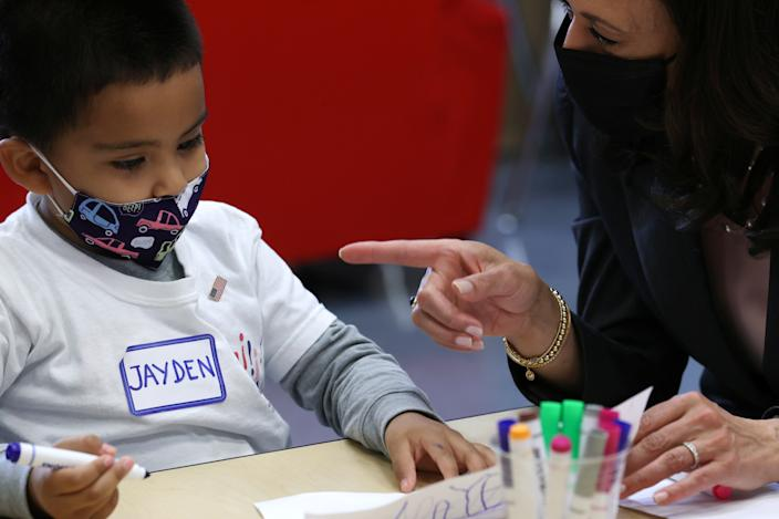 U.S. Vice President Kamala Harris gives her flag pin to Jayden Vello as she visits his classroom at CentroNia, a bilingual early childhood education center, to highlight child tax credit programs, in Washington, U.S. June 11, 2021.  REUTERS/Jonathan Ernst