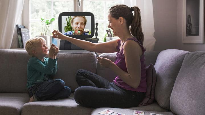 A woman and child high-fiving while on video chat with a man smiling
