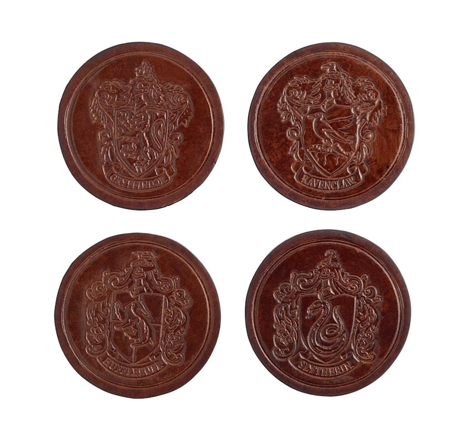 """<p>Your kids won't mind you yelling to put their glasses on coasters if you have these <a rel=""""nofollow noopener"""" href=""""https://www.popsugar.com/buy/House-Crest-Coasters-362141?p_name=House%20Crest%20Coasters&retailer=potterybarn.com&price=25&evar1=moms%3Aus&evar9=45219298&evar98=https%3A%2F%2Fwww.popsugar.com%2Fmoms%2Fphoto-gallery%2F45219298%2Fimage%2F45219320%2FHouse-Crest-Coasters&list1=home%20decor%2Charry%20potter%2Cpottery%20barn%2Charry%20potter%20home%20decor%2Charry%20potter%20home%2Chome%20shopping&prop13=desktop&pdata=1"""" target=""""_blank"""" data-ylk=""""slk:House Crest Coasters"""" class=""""link rapid-noclick-resp"""">House Crest Coasters</a> ($25 for a set of four).</p>"""