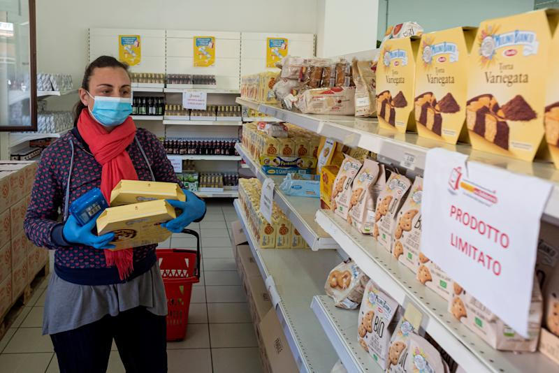 ROME, ITALY - MAY 09: A woman takes food from the shelves at the emporium of solidarity of the diocesan Caritas of Rome to Casilino Bridge, a supermarket for families in need on May 09, 2020 in Rome, Italy. The emporium, enables families that are in difficulty to collect free basic necessities due to the coronavirus (COVID-19) pandemic with access for families in need increasing from 60 per day to 150 per day. Italy was the first country to impose a nationwide lockdown to stem the transmission of the Coronavirus (COVID-19), and its restaurants, theaters and many other businesses remain closed. (Photo by Stefano Montesi - Corbis/ Getty Images) (Photo: Stefano Montesi - Corbis via Getty Images)