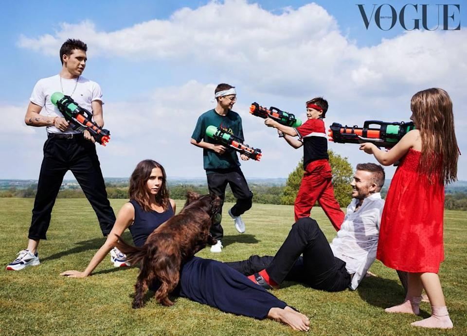 The Beckhams enjoying a water pistol fight on the inside pages of British Vogue's October issue. [Photo: Getty]