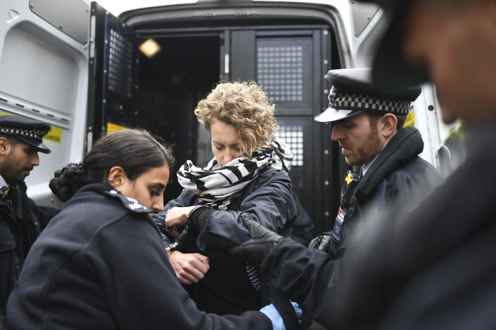 Police officers arrest a demonstrator during an Extinction Rebellion Protest in London, Monday, Oct. 7, 2019. (Photo: Alberto Pezzali/AP)