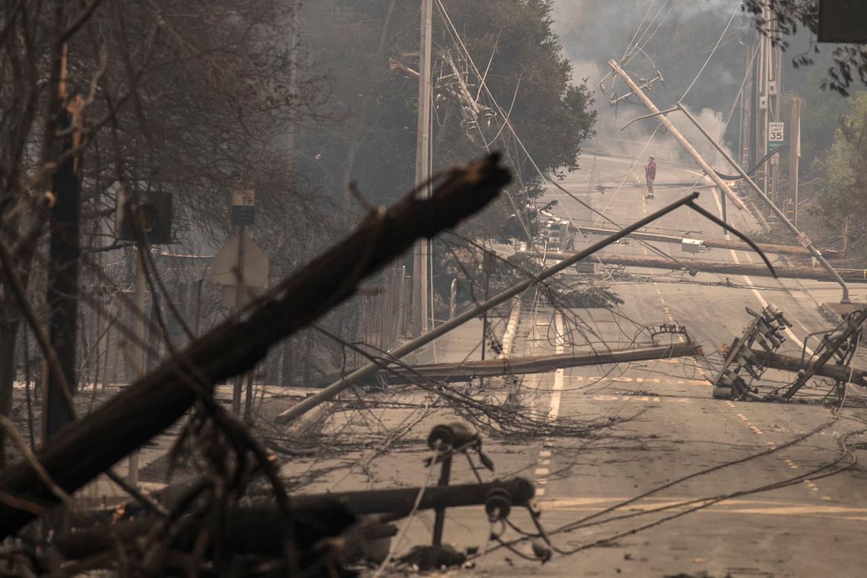 Power poles and lines block a street at Brookdale and Aaron Drive in Hidden Valley, where most of the homes were destroyed by fire in Santa Rosa.