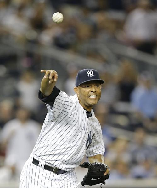 New York Yankees relief pitcher Mariano Rivera (42) throws to first on Rajai Davis infield grounder in the second baseball game of a doubleheader against the Toronto Blue Jays at Yankee Stadium, Tuesday, Aug. 20, 2013, in New York. (AP Photo/Kathy Willens)