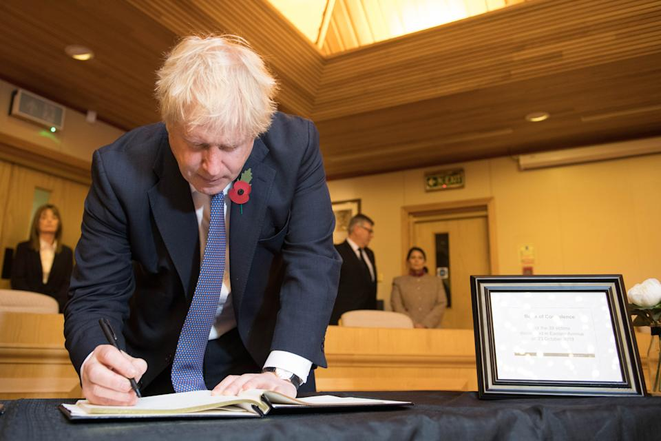 Prime Minister Boris Johnson signs a book of condolence, during a visit to Thurrock Council Offices in Essex after the bodies of 39 people were found in a lorry container last week.
