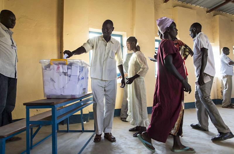 People cast their votes in an abandoned school used as a polling center in the disputed border region of Abyei, whose ownership is claimed by both Sudan and South Sudan, Sunday, Oct. 27, 2013. Hundreds of people in the disputed border region of Abyei voted Sunday in a referendum that they hope will decide whether they join Sudan or South Sudan, a local leader said, but the exercise lacked the official backing of either of the two governments. (AP Photo/Mackenzie Knowles-Coursin)