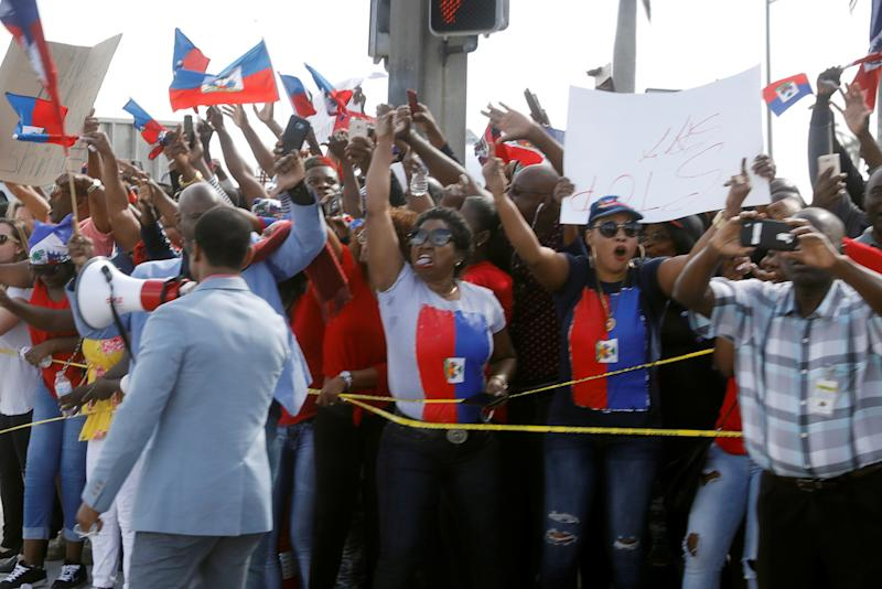 Demonstrators hold up Haitian flags and shout as President Donald Trump's motorcade passes in West Palm Beach, Florida, on Jan. 15, 2018.