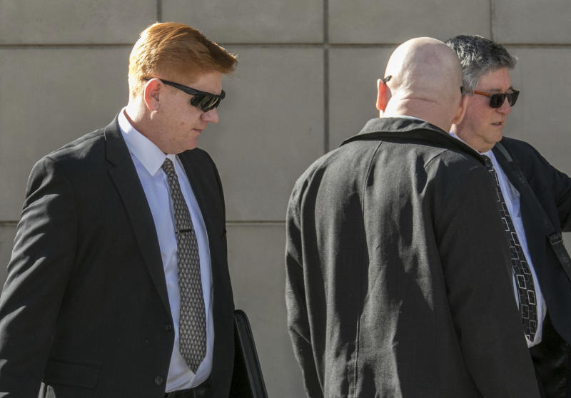 FILE - In this March 21, 2018, file photo, Border Patrol agent Lonnie Swartz, left, makes his way to the U.S. District Court building in downtown Tucson, Ariz., where opening arguments are scheduled to begin in the his murder trial in Tucson. Federal prosecutors on Thursday, Dec. 6, 2018, said they would not pursue another trial against Swartz, who was twice acquitted. (Ron Medvescek/Arizona Daily Star via AP)