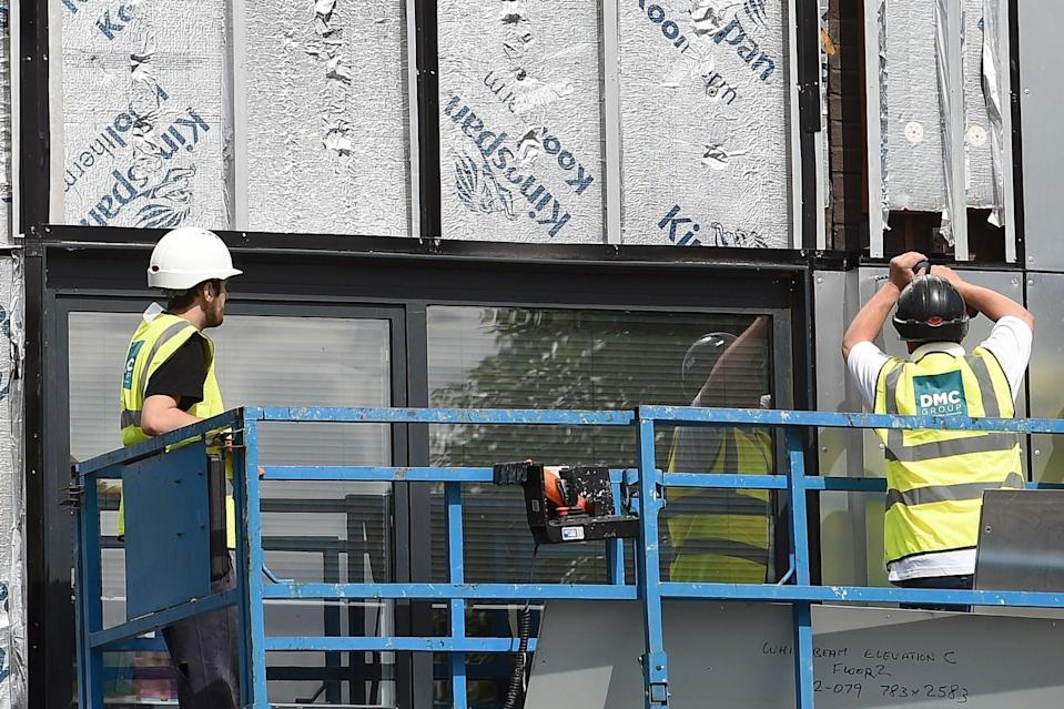 <p>Workers remove cladding from a tower block</p> (AFP via Getty Images)