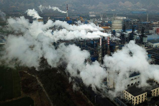 Smoke and steam rise from a coal processing plant that produces carbon black, an ingredient in steel manufacturing, in Hejin in central China's Shanxi Province.