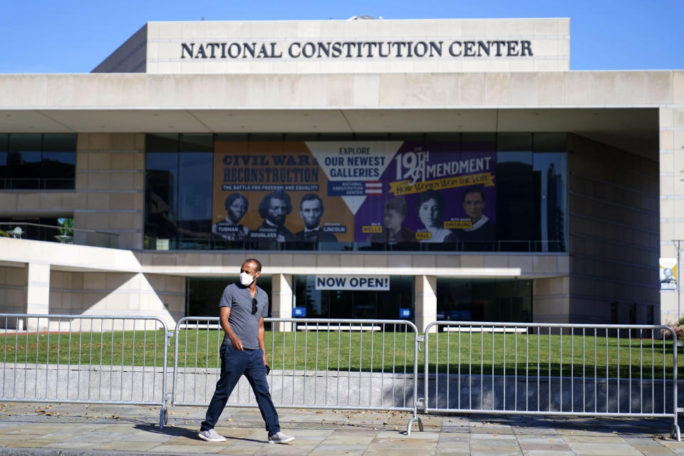 FILE—In this file photo from Oct. 15, 2020, a man walks past the National Constitution Center in Philadelphia. The facade bearing the First Amendment of the U.S. Constitution that was on the front of the Newseum in Washington that closed in December of 2019, will be reinstalled at The National Constitution Center in an atrium overlooking Independence Hall.(AP Photo/Matt Slocum, File)