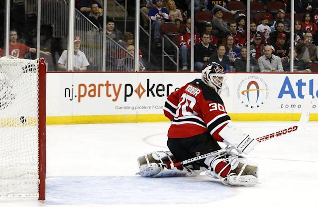 A shot by New York Islanders' Anders Lee enters the net of New Jersey Devils goalie Martin Brodeur (30) for a goal during the first period of an NHL hockey game on Friday, April 11, 2014, in Newark, N.J. (AP Photo/Julio Cortez)