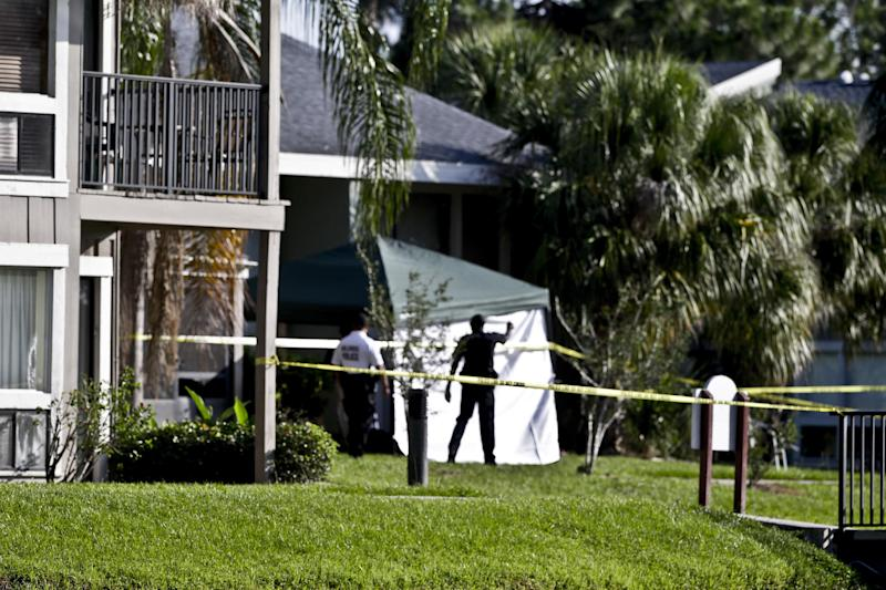Investigators stand outside an apartment complex where a man was fatally shot when a team of FBI agents swarmed his home early Wednesday, May 22, 2013, in Orlando, Fla. The FBI says the man, being questioned by authorities in the Boston bombing probe, was fatally shot when he initiated a violent confrontation. (AP Photo/John Raoux)