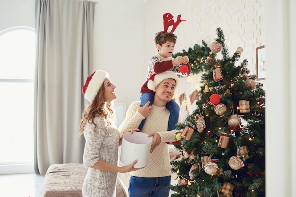 Mother, father and son in sweaters paint the Christmas tree in the house.