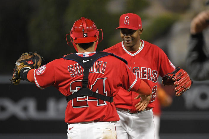 Los Angeles Angels catcher Kurt Suzuki, left, and relief pitcher Raisel Iglesias congratulate each other after the. Angels defeated the Texas Rangers 6-2 in a baseball game Tuesday, April 20, 2021, in Anaheim, Calif. (AP Photo/Mark J. Terrill)