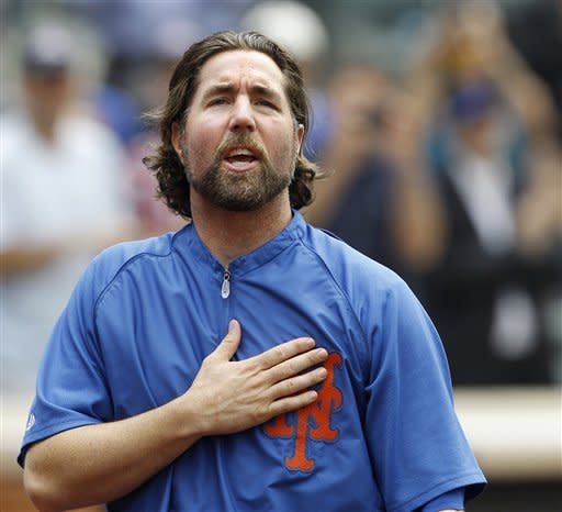 New York Mets starting pitcher R.A. Dickey puts his hand to his heart as the thanks the fans as he celebrates his 20th victory of the season after the Mets 6-5 win against the Pittsburgh Pirates in a baseball game at Citi Field in New York, Thursday, Sept. 27, 2012. (AP Photo/Kathy Willens)