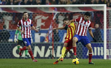 Barcelona's Jordi Alba (C) fights for the ball with Atletico Madrid's Diego Costa (R) during their Spanish first division soccer match at the Vicente Calderon stadium in Madrid January 11, 2014. REUTERS/Juan Medina