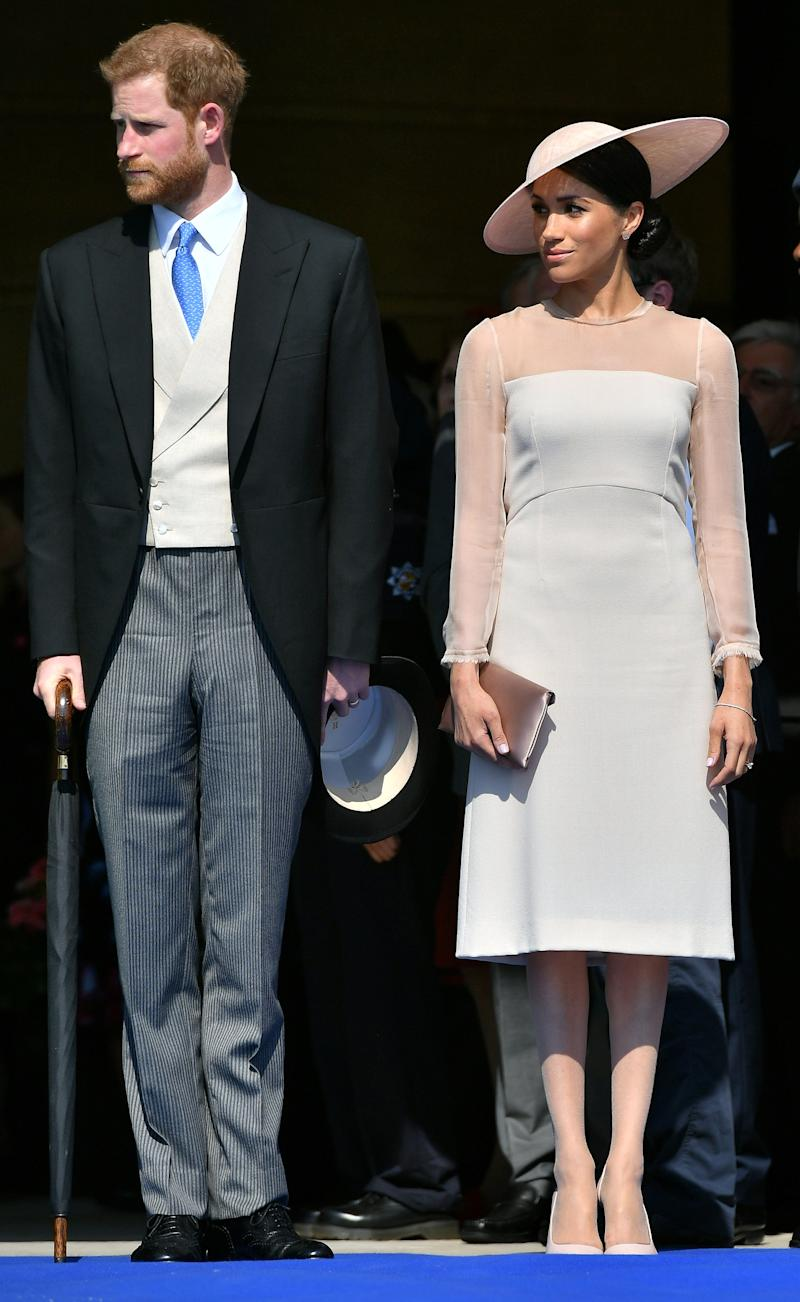 Britain's Prince Harry, Duke of Sussex (L), and his new wife, Britain's Meghan, Duchess of Sussex, attend the Prince of Wales's 70th Birthday Garden Party at Buckingham Palace in London on May 22, 2018. - The Prince of Wales and The Duchess of Cornwall hosted a Garden Party to celebrate the work of The Prince's Charities in the year of Prince Charles's 70th Birthday. (Photo by Dominic Lipinski / POOL / AFP) (Photo credit should read DOMINIC LIPINSKI/AFP via Getty Images)
